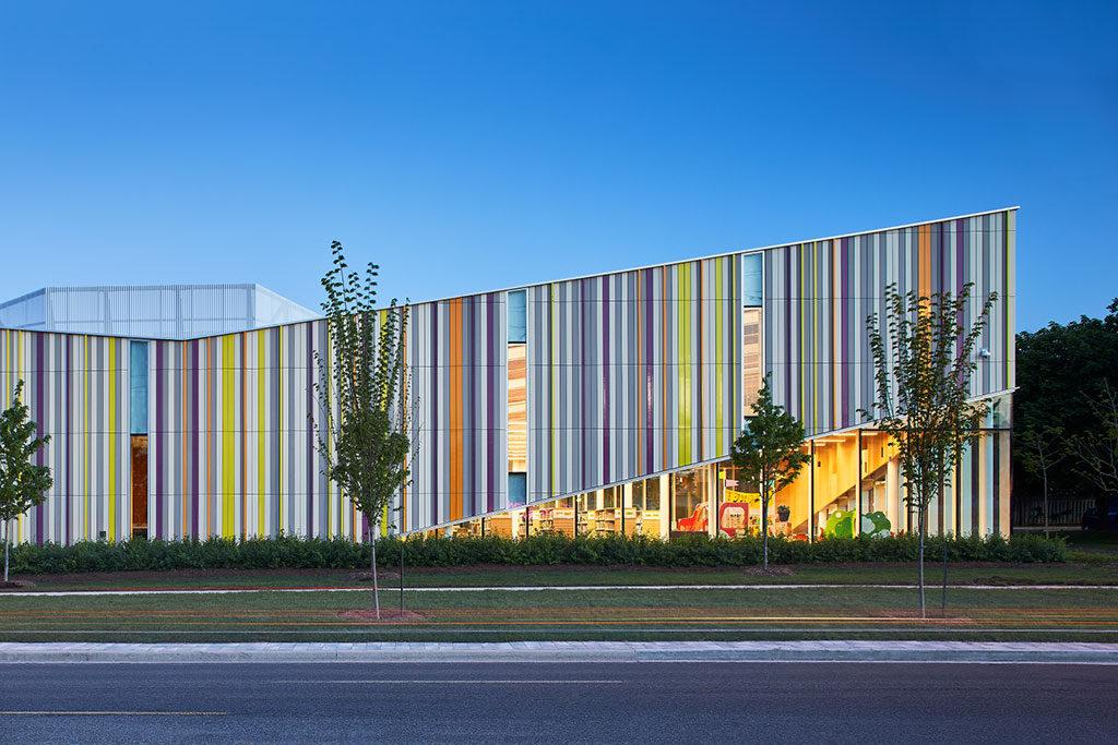 Bâtiment horizontal aux murs extérieurs obliques formés de lamelles verticales aux couleurs vives.