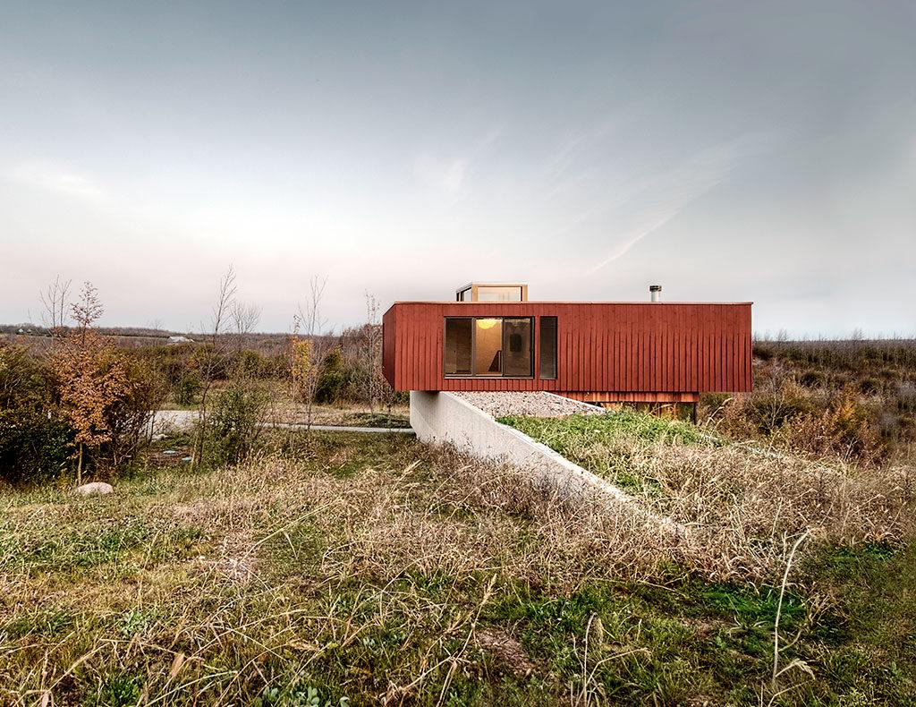Construction trapue en porte-à-faux revêtue de planches de bois couleur rouille; long mur en béton percé de fenêtres à flanc de colline.