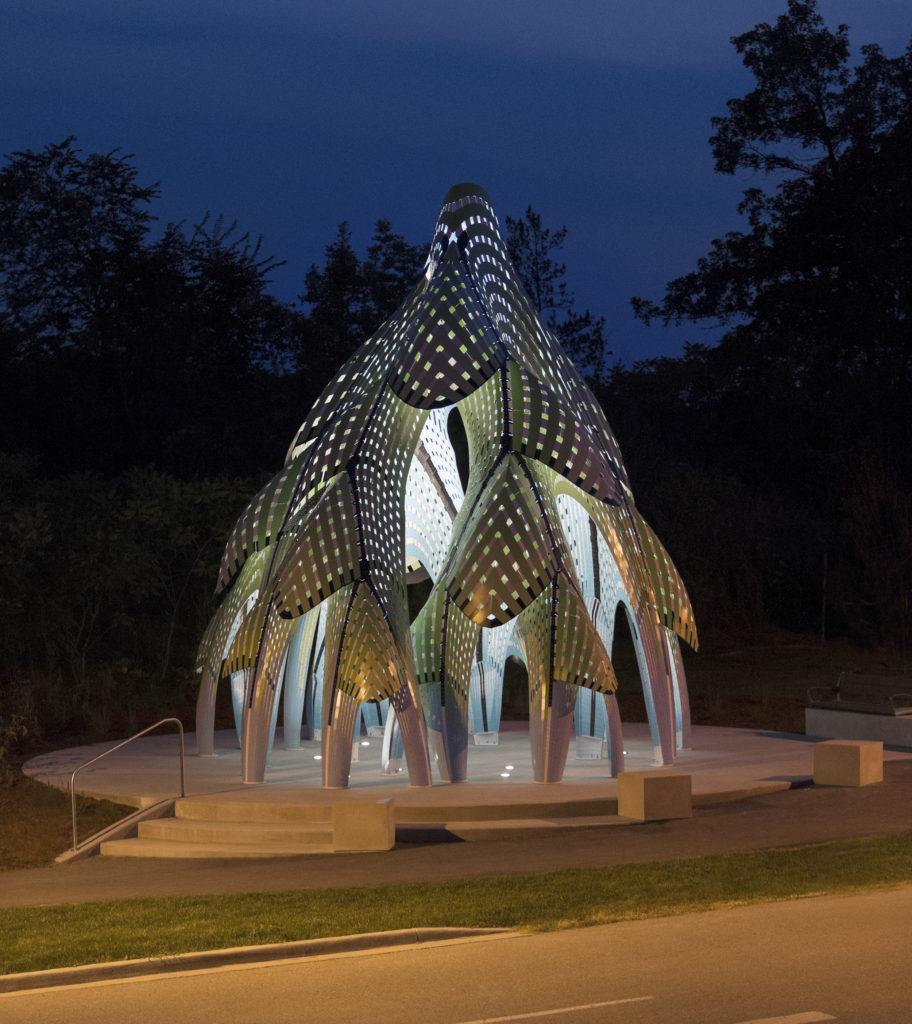 Pavillon conique ouvert en forme d'arbre fait de baguettes d'aluminium courbées.