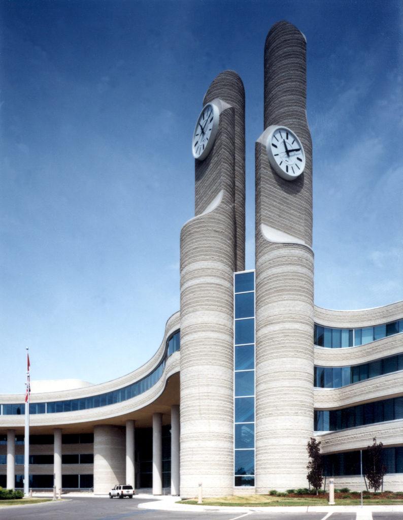 Bâtiment de quatre étages pourvu de rangées de fenêtres ininterrompues de forme courbe et de deux grandes tours d'horloge à côté de l'entrée.