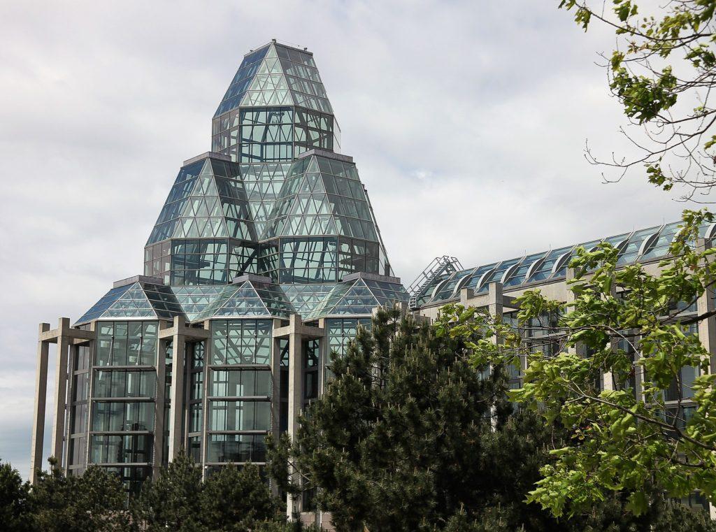 Bâtiment de verre, d'acier et de pierre orné d'un ensemble complexe de tours vitrées au-dessus de l'entrée.