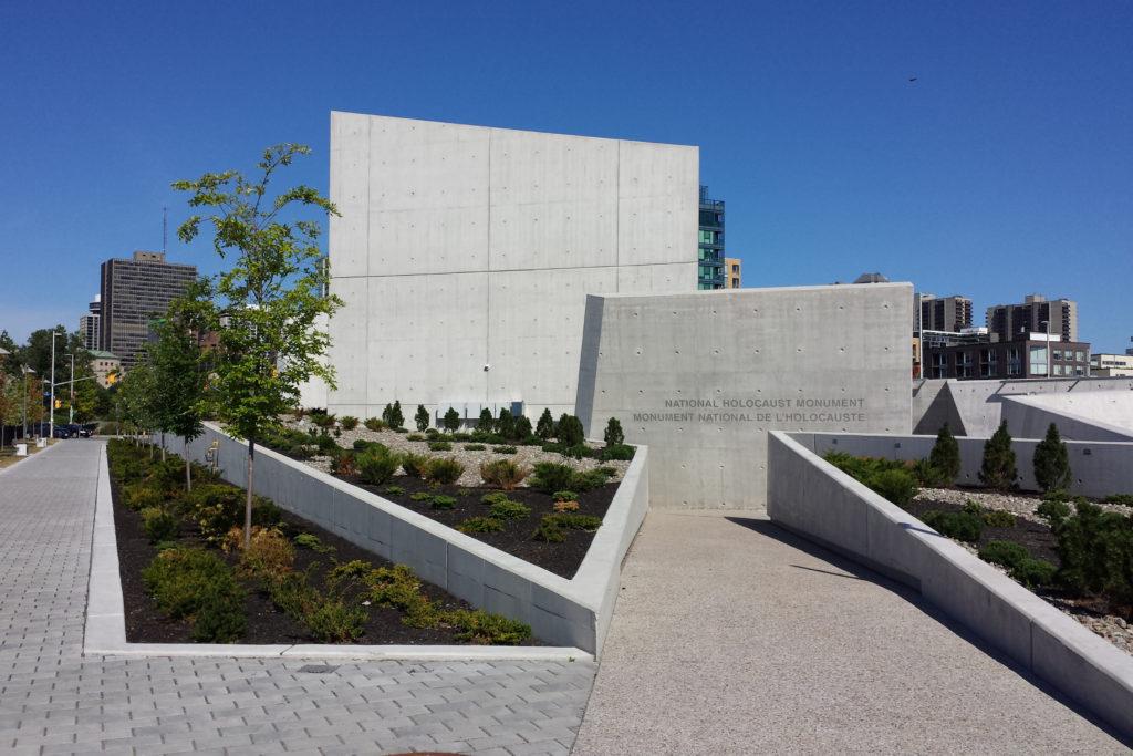 Bâtiment angulaire en béton; allées bordées de murs de béton inclinés.