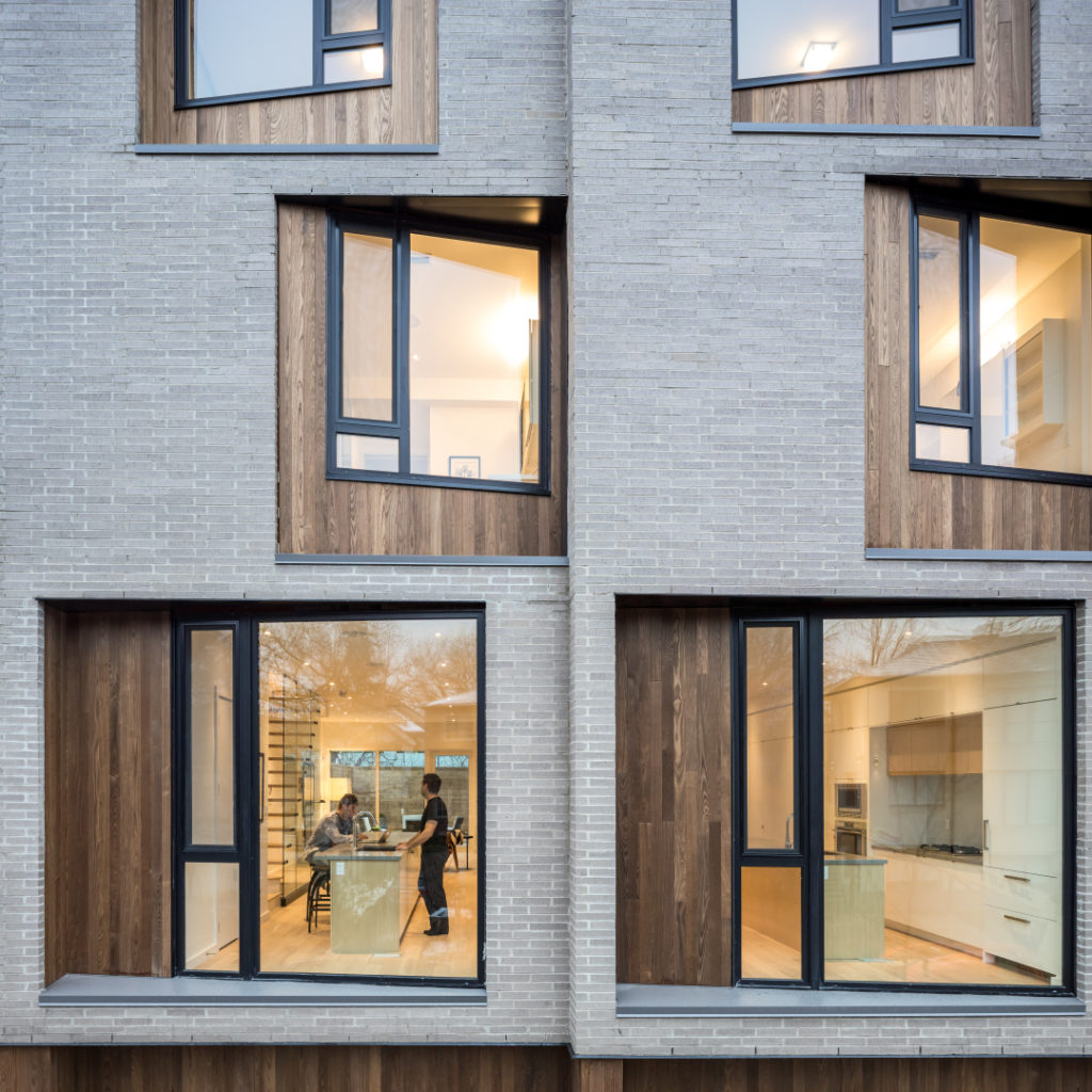 Façade d'immeuble d'habitation en brique beige; fenêtres encastrées en angle et encadrées de panneaux de bois.