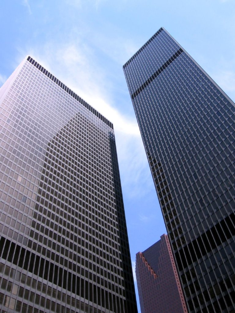 Two tall, simple glass-and-steel buildings viewed from below.