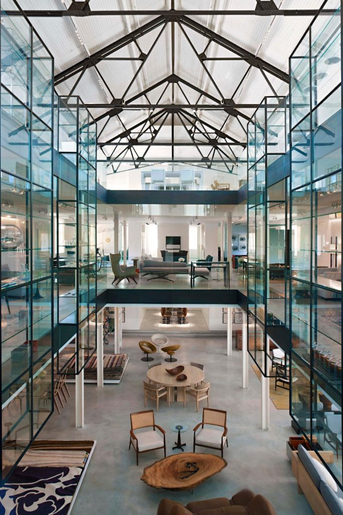 Large open interior space with glass walls, steel frame, and translucent ceiling. Upper levels surround open central space.