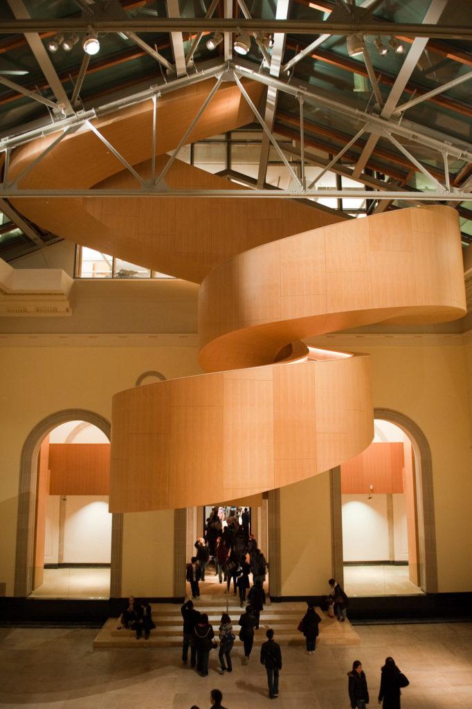 Escalier en colimaçon aux formes exubérantes revêtu de bois lisse dans une galerie dégagée; haut plafond vitré tendu d'une structure en métal.