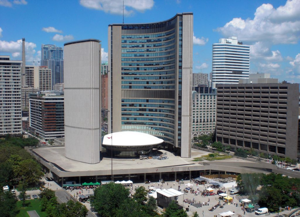 Two tall curved buildings in glass and concrete flank a low saucer-shaped building with a domed white top.