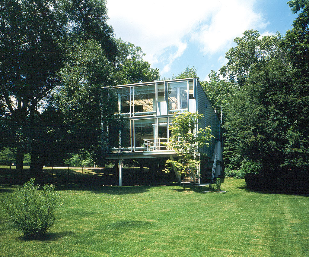 Maison rectangulaire à charpente d'acier et aux murs vitrés.