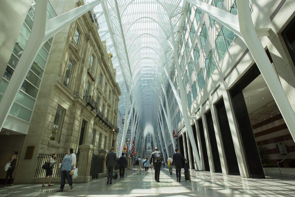 Allée piétonne traversant des rangées de bâtiments; voûte vitrée six étages au-dessus, étayée par de majestueux supports en acier.