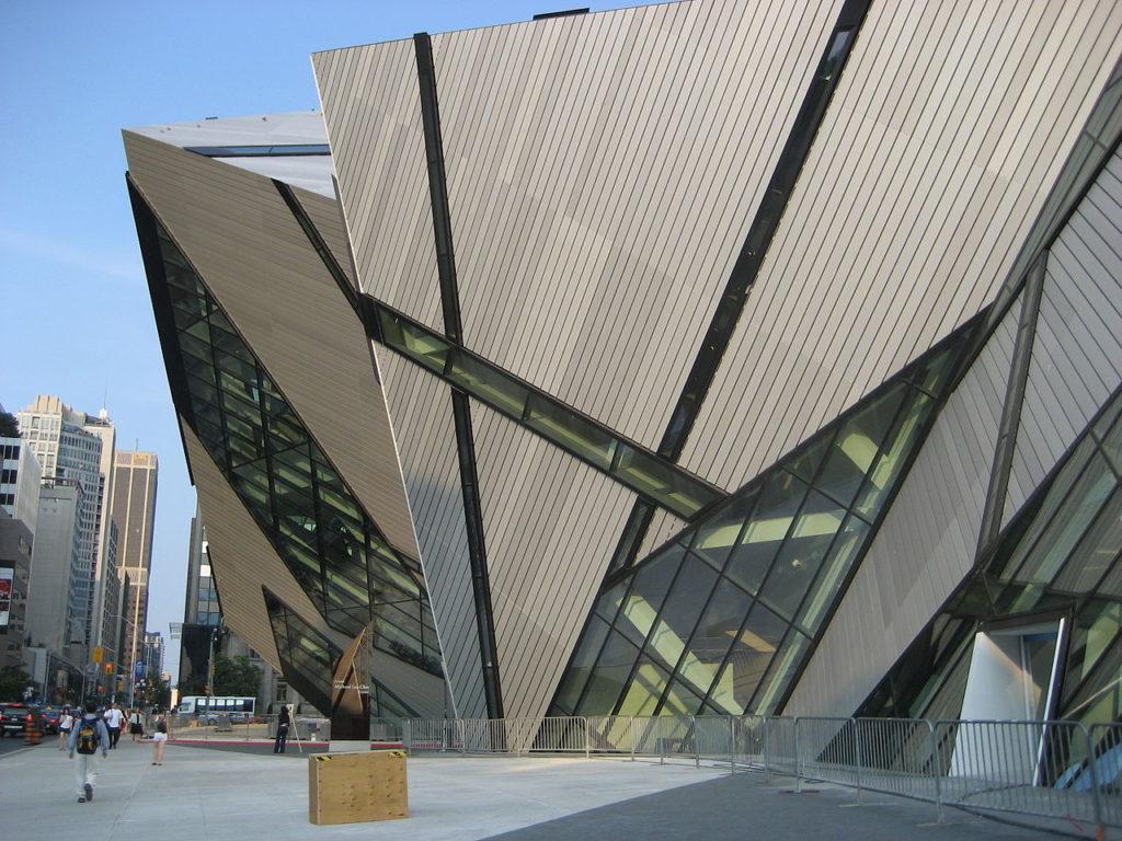 Structure contemporaine aux formes angulaires atypiques en métal et en verre qui semblent émerger de l'édifice et planer au-dessus du trottoir.