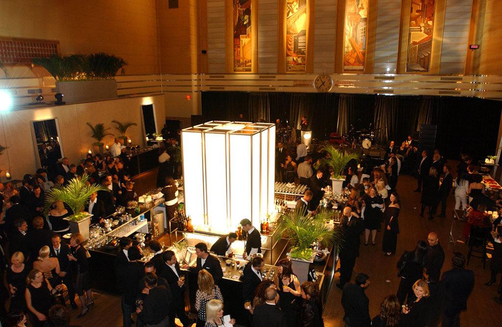 Espace intérieur orné de peintures murales et de dorures; grand cube illuminé au centre.