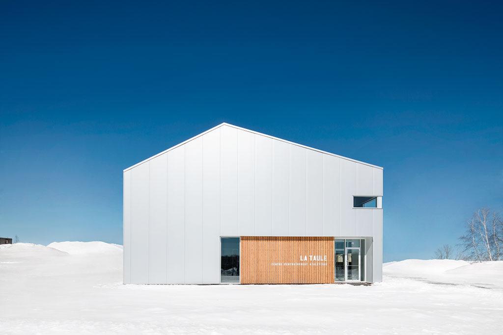 Construction simple, semblable à une grange avec sa façade d'acier blanc et son entrée faite de panneaux de bois et de verre, dans un décor enneigé.