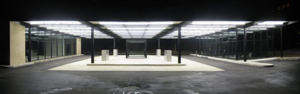 Construction partiellement ouverte; large toit plat et parois de verre aux extrémités.