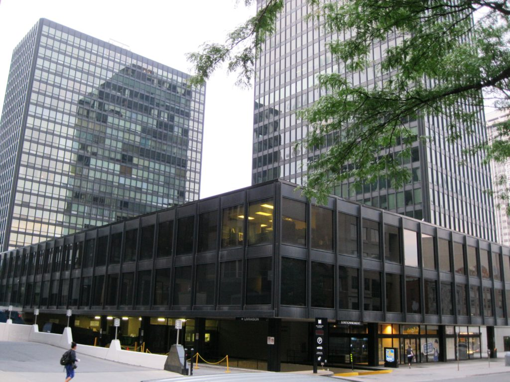 A group of three simple, rectangular buildings of glass and steel. A short horizonal building in the foreground with a taller building in the background on the left and the tallest building in the background on the right.
