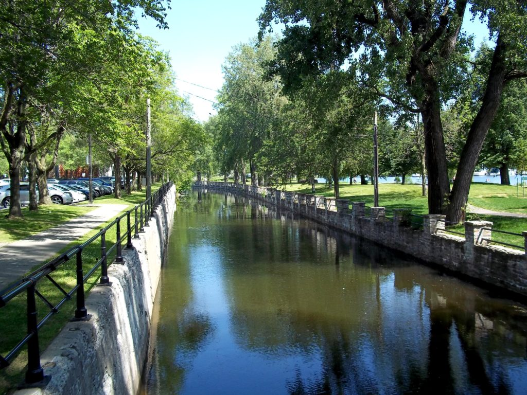 Long narrow canal flanked by park space, lined with trees and paved paths