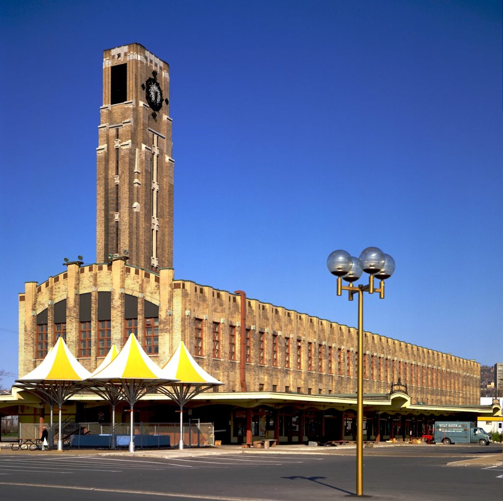 Long arched building of brick, glass and concrete, with tall stepped clock tower near the front.