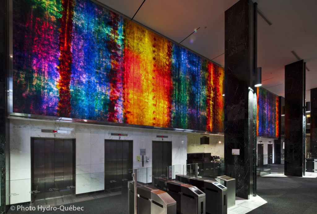 Interior space with long rectangular panel of an abstract design in colored glass, lit from behind, forming the wall above a bank of elevators.