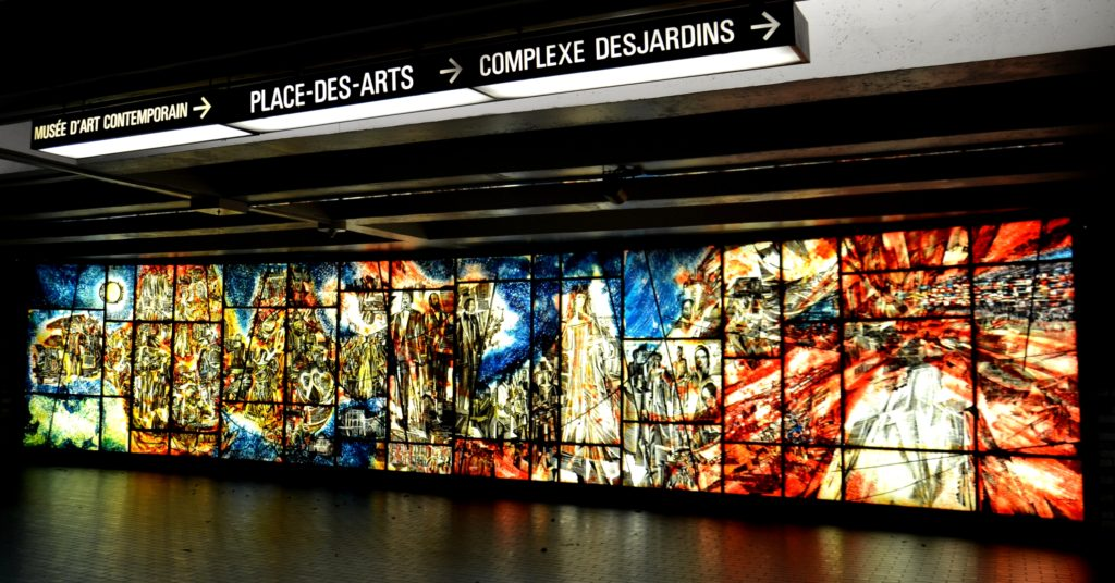 Long rectangular mural of a series of designs in colored glass.