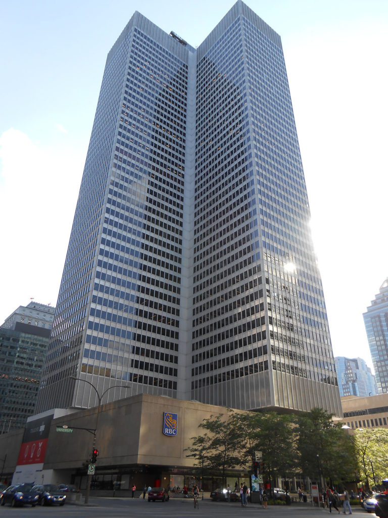 Two tall buildings in glass and concrete connected at one corner.