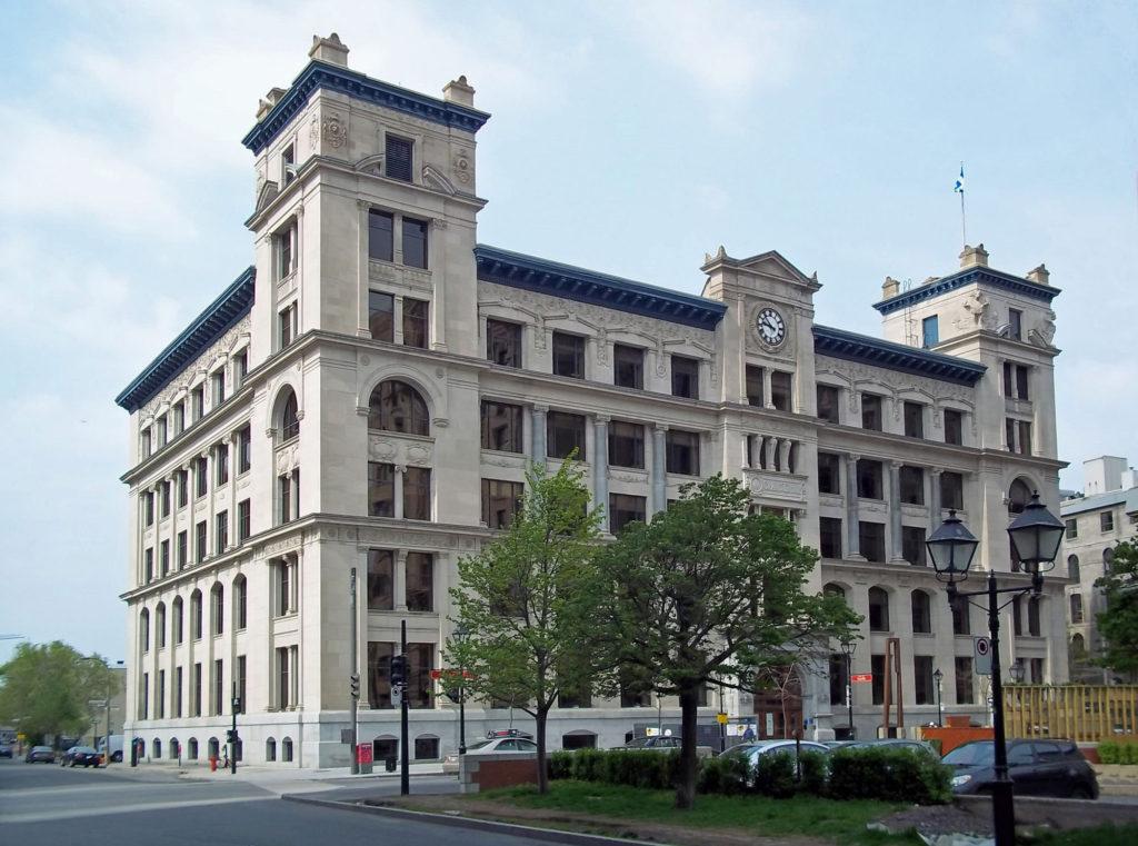 Bâtiment rectangulaire du début du XXesiècle flanqué de deux tours dominant une tour d'horloge centrale.