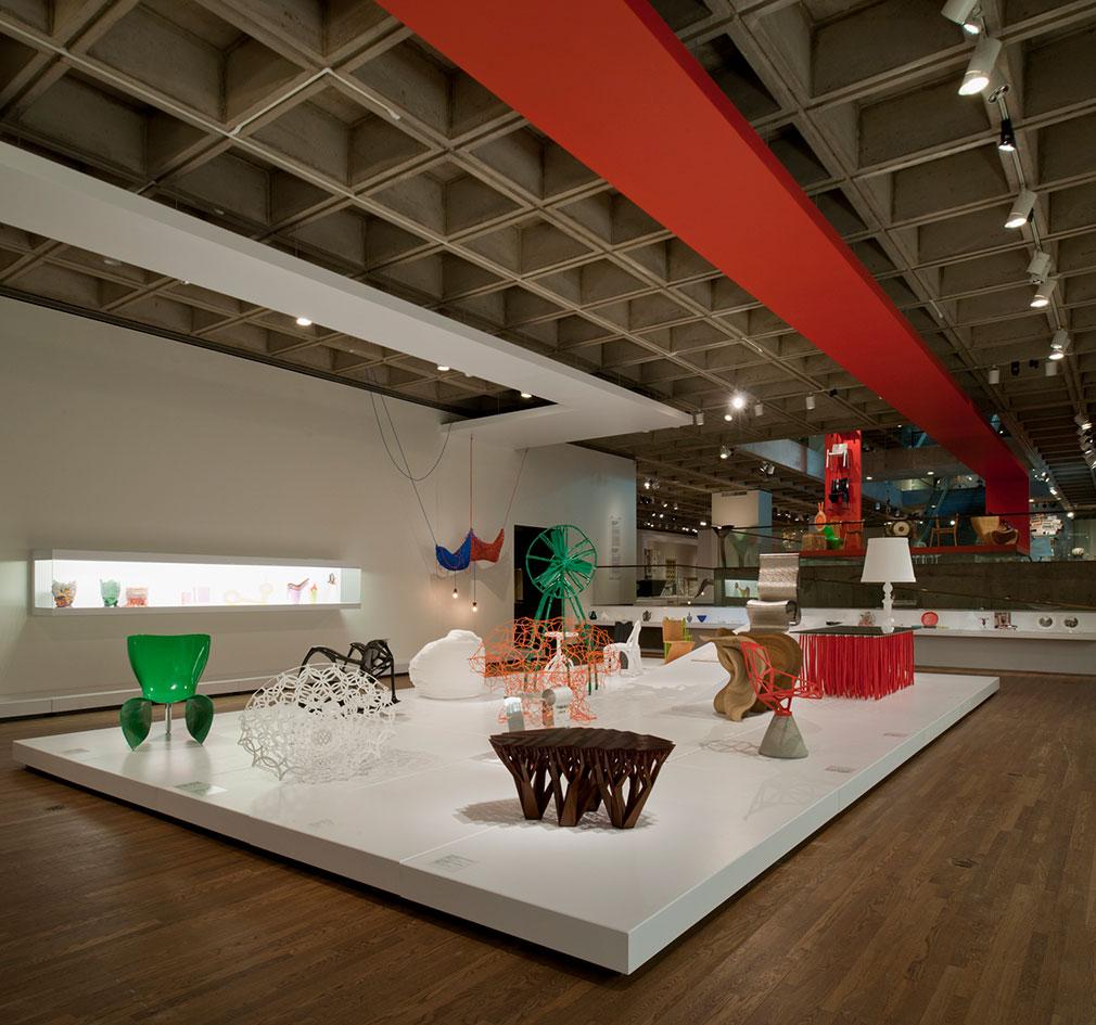 Vue intérieure du musée et de l'installation; grande plateforme rectangulaire blanche accueillant des meubles colorés.