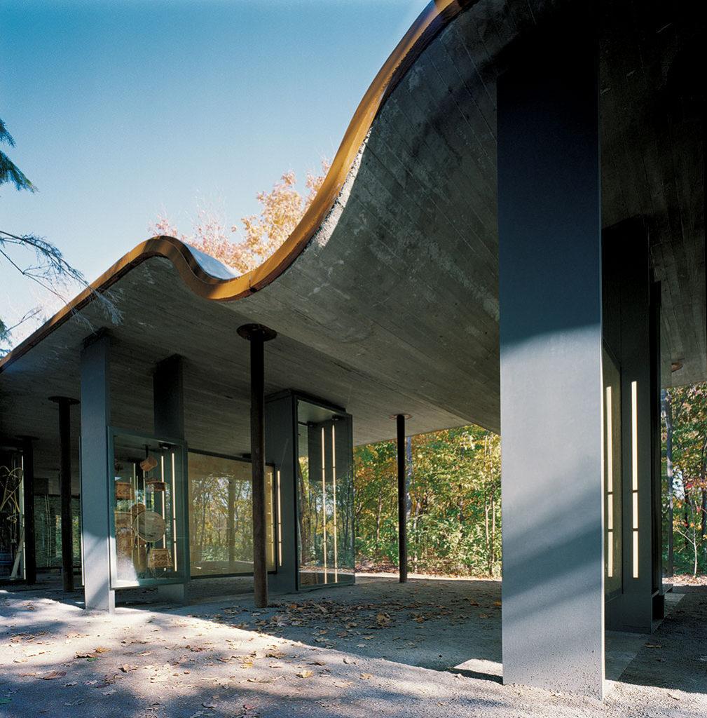Pavillon au toit de bois ondulé reposant sur des piliers en acier.