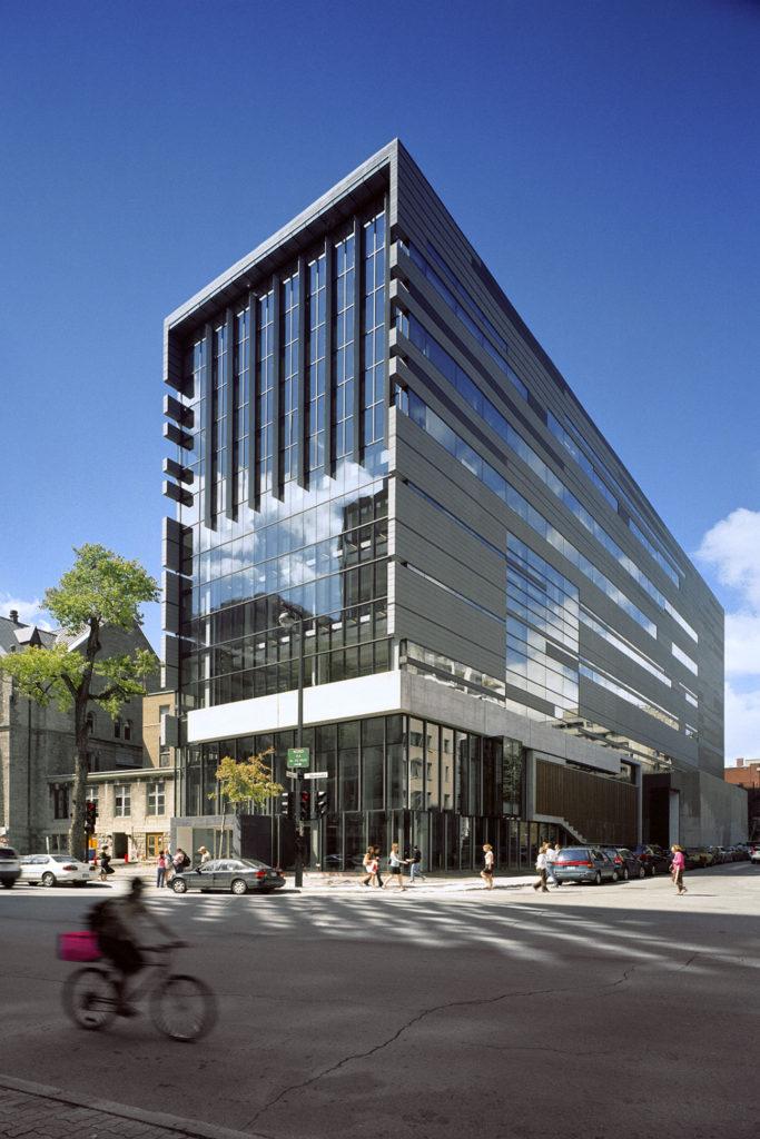 Bâtiment rectangulaire de dix étages en verre et en béton; rez-de-chaussée en retrait.