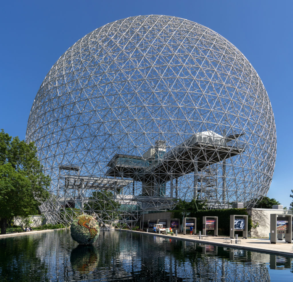 Grand pavillon en forme de sphère, charpente en treillis composée de tubes d'acier posée sur un bâtiment multiniveaux doté d'une plateforme en saillie