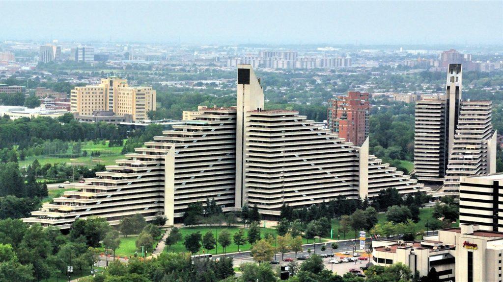 Immeuble d'habitation pyramidal pourvu d'une tour centrale; bâtiment identique à gauche, à l'arrière-plan.