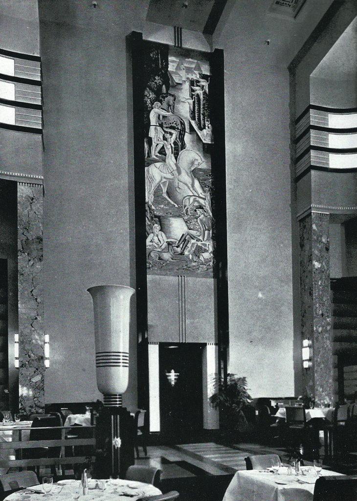 Intérieur du restaurant de style Art déco avec son haut plafond. Murale occupant l'espace vertical au-dessus de l'ascenseur, vase décoratif classique à l'avant-plan.