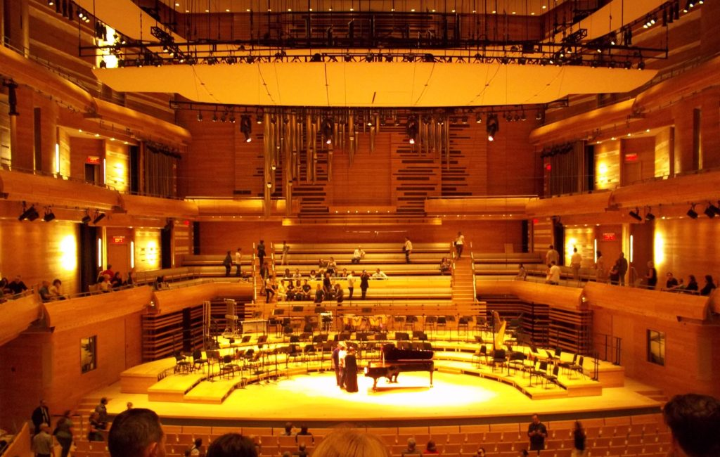Large concert hall with walls of wood and large panels suspended above the stage.