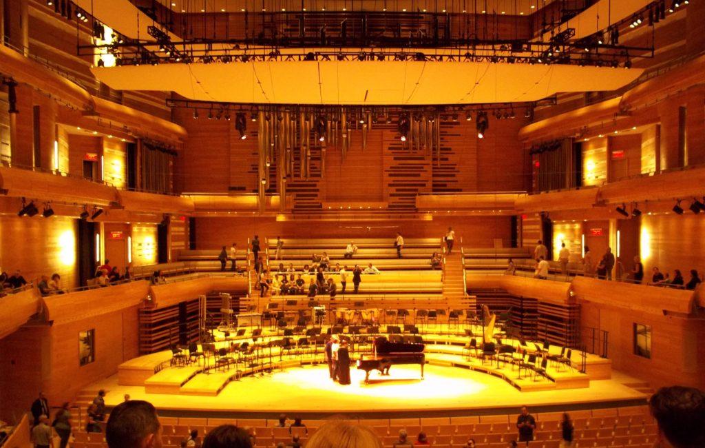 Grande salle de concert dotée de murs en bois et de grands panneaux suspendus au-dessus de la scène.