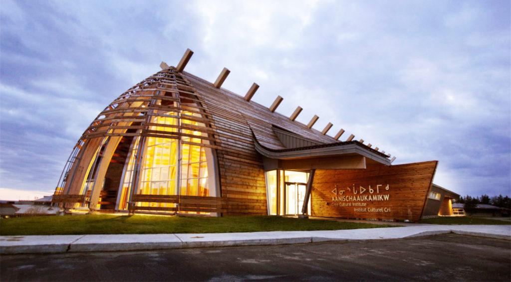 Construction voûtée en bois, mur d'extrémité vitré et poutres entrecroisées jaillissant du toit.