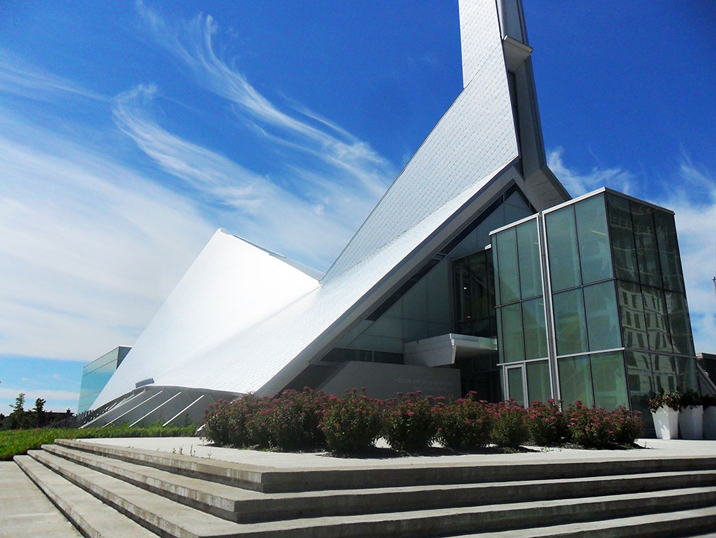 Sweeping and curving metallic building surmounted by a geometric steeple.