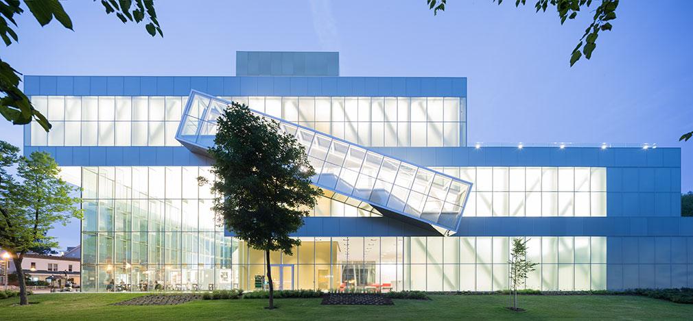 Bâtiment composé de deux structures rectangulaires en verre et en acier, la section supérieure faisant saillie au-dessus du rez-de-chaussée.