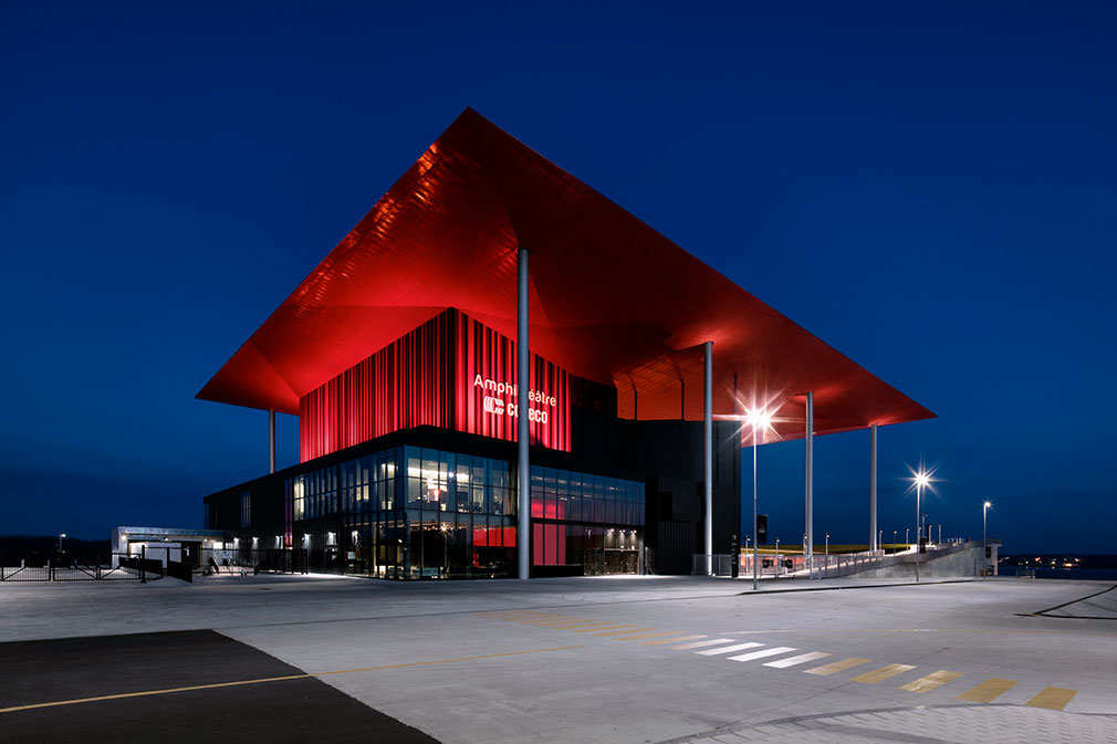 Glass and steel building with dramatically extended red metal roof supported by metal columns.