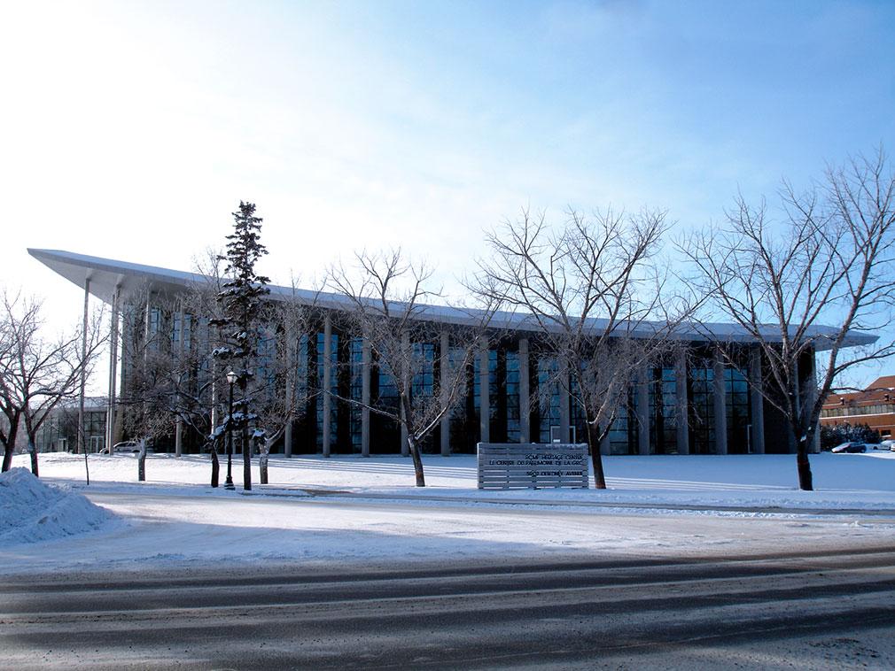 Bâtiment en verre et en béton surmonté d'un grand toit en porte-à-faux s'appuyant sur une série de colonnes.