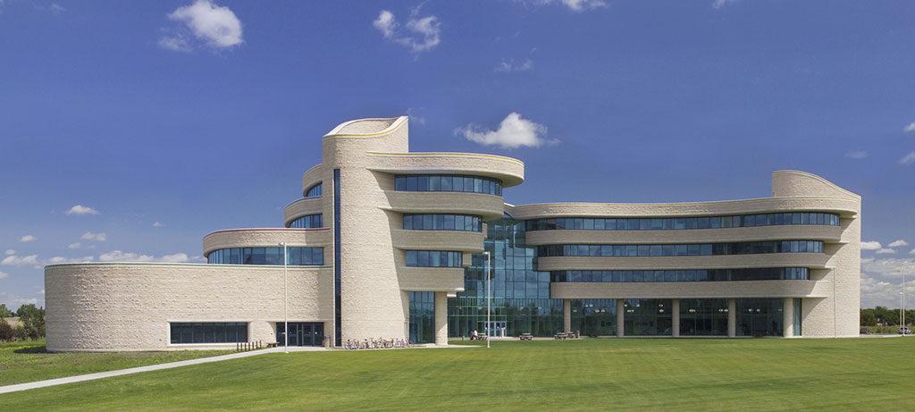 Bâtiment semi-circulaire formé d'étages ondulants évoquant des bandes de pierre et de verre, flanqué de deux tours cylindriques.