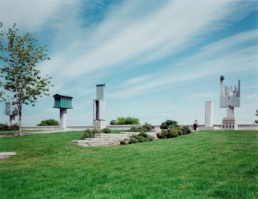 Socles disposés par intervalle sur une esplanade, chacun surmonté de la maquette d'un bâtiment.