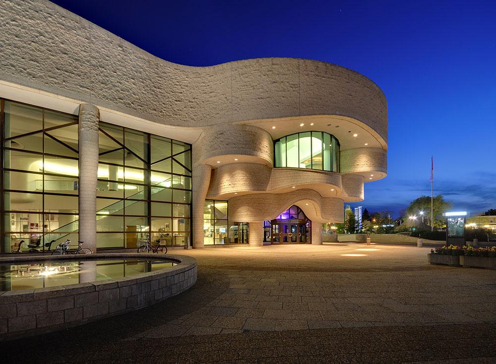 Grand bâtiment horizontal de pierres pâles et de verre, coiffé d'une coupole à l'une de ses extrémités. À ses pieds se trouve une place composée de larges allées sinueuses et d'escaliers.
