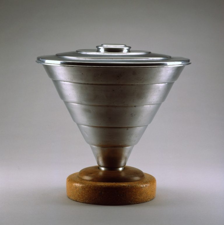 Conical metal pail with circular metal lid and tapering down to a circular cork base.