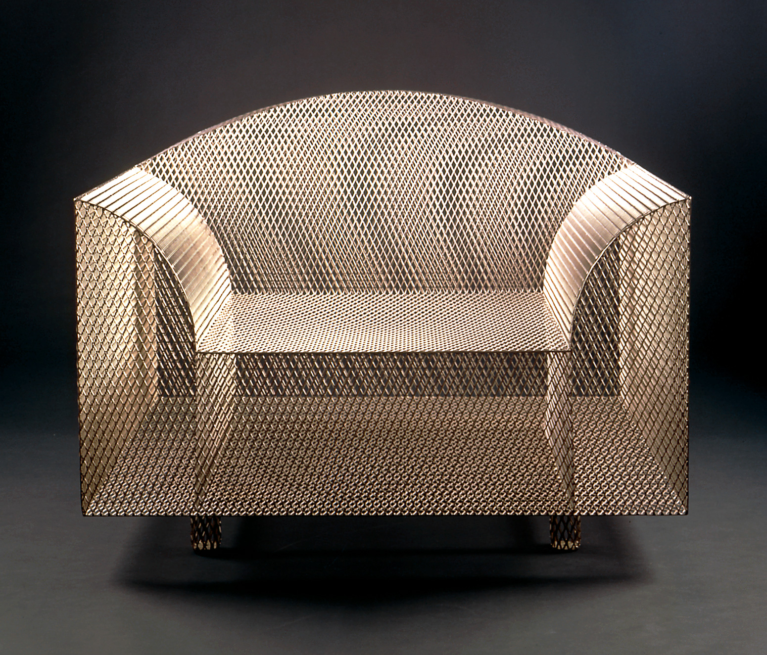 Armchair of metal mesh with rectangular base and curved arms and back.