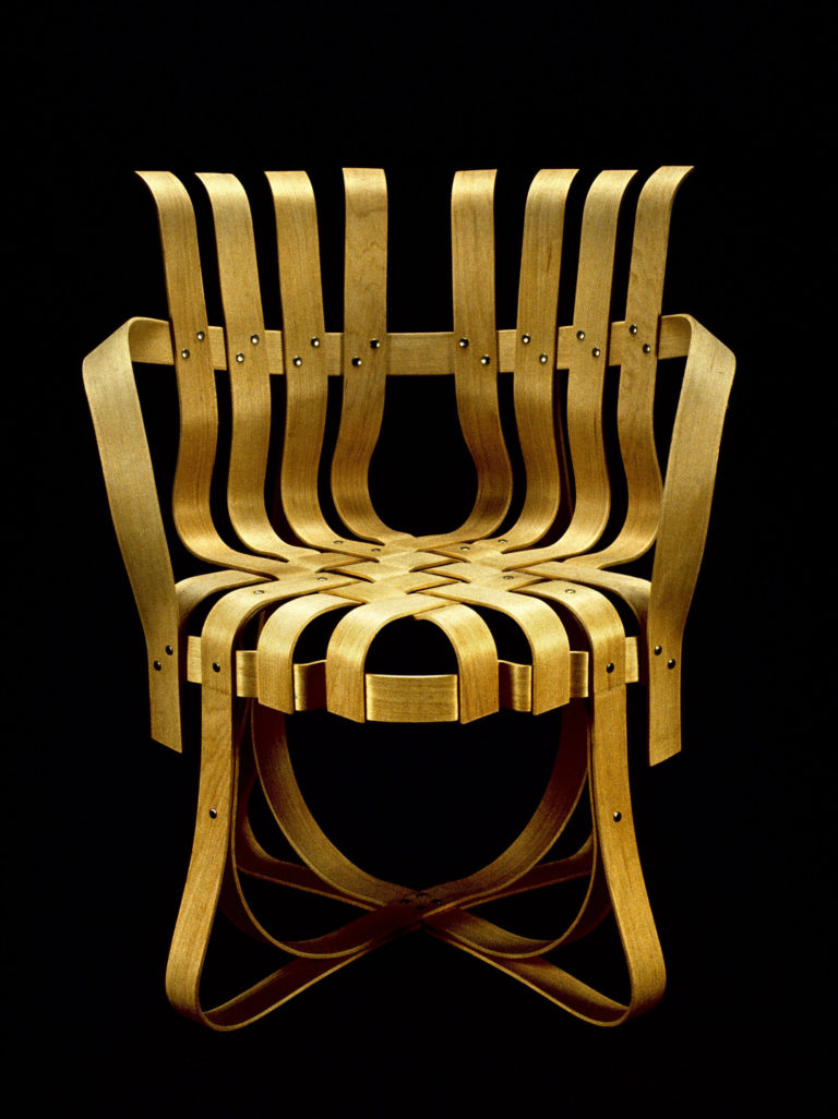 Armchair composed of numerous plywood strips bent to form curving arms, back, and legs, and woven together to form the seat.