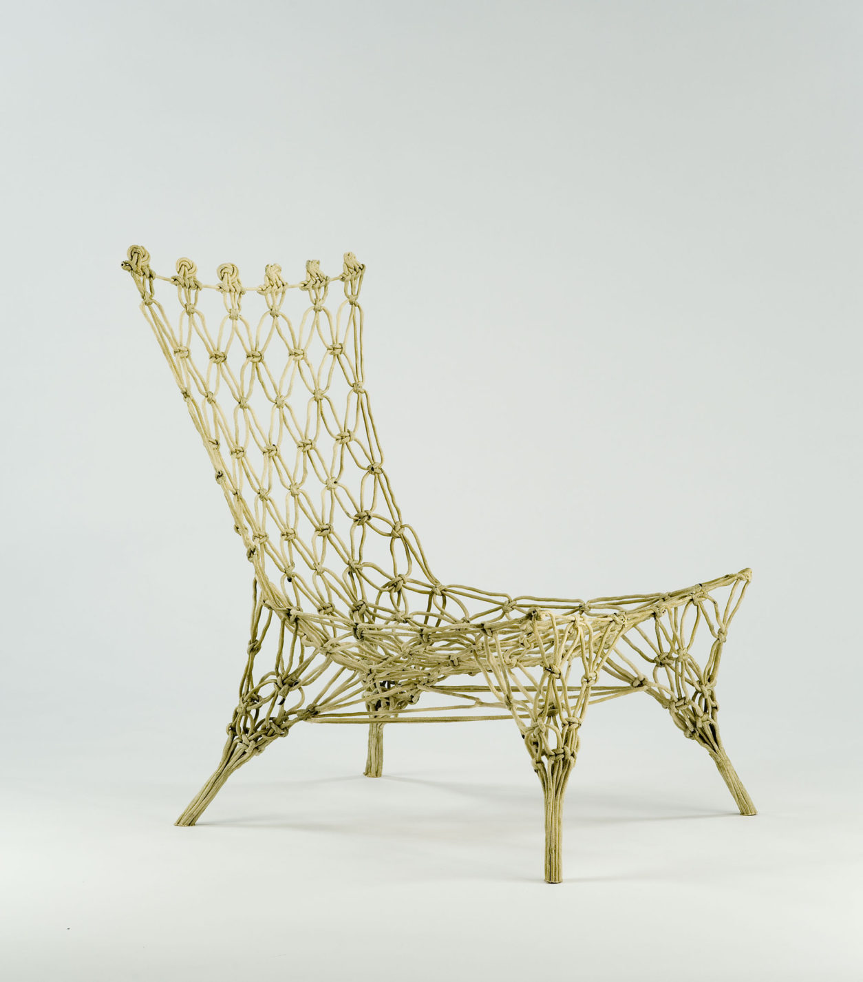 Chair formed of stiffened knotted rope, similar to a macramé net frozen in space.