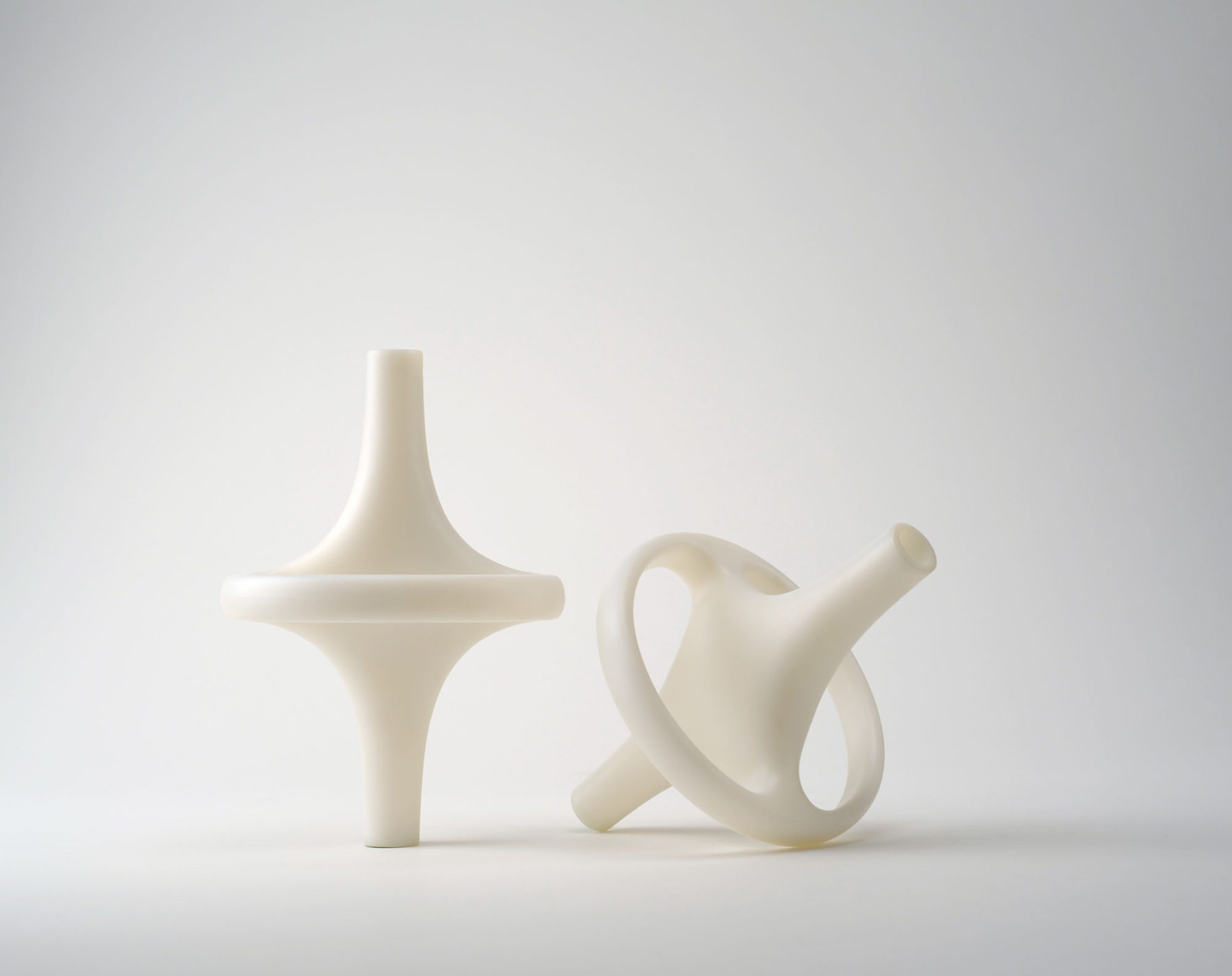 Two molded white plastic vases, each composed of long tube that widens at the center to connect to a surrounding ring.