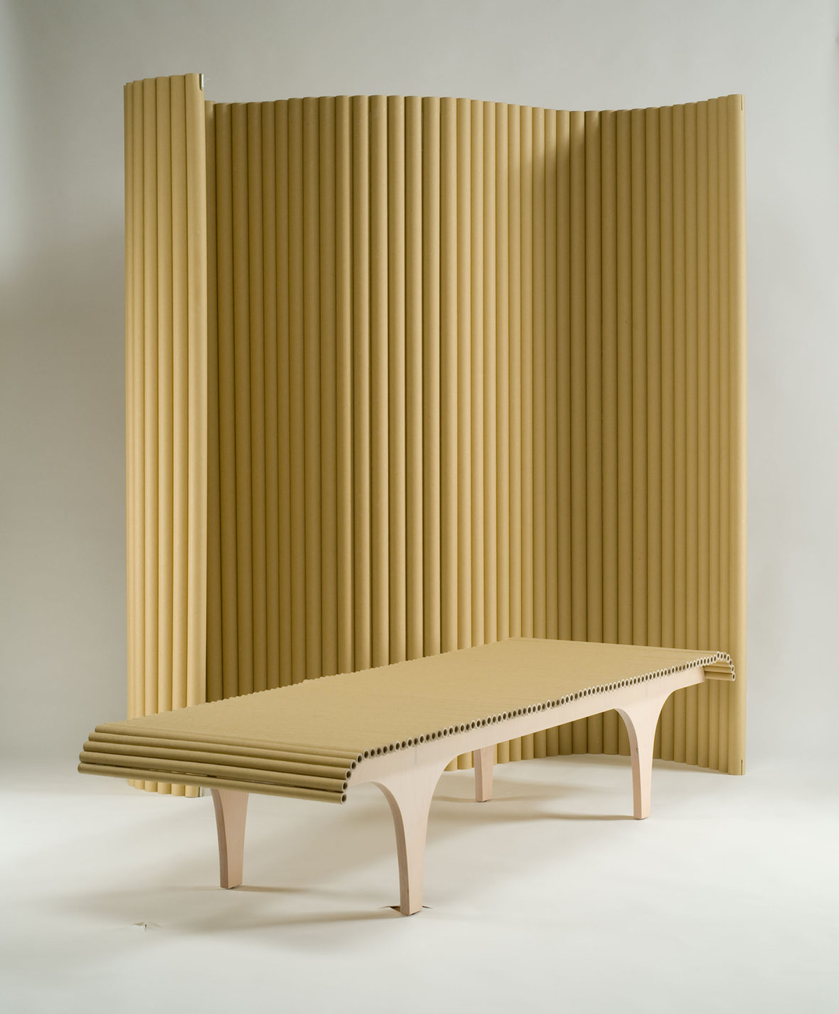 Tall adjustable screen made of vertical cardboard tubes and wood-framed bench with cardboard-tube seat.