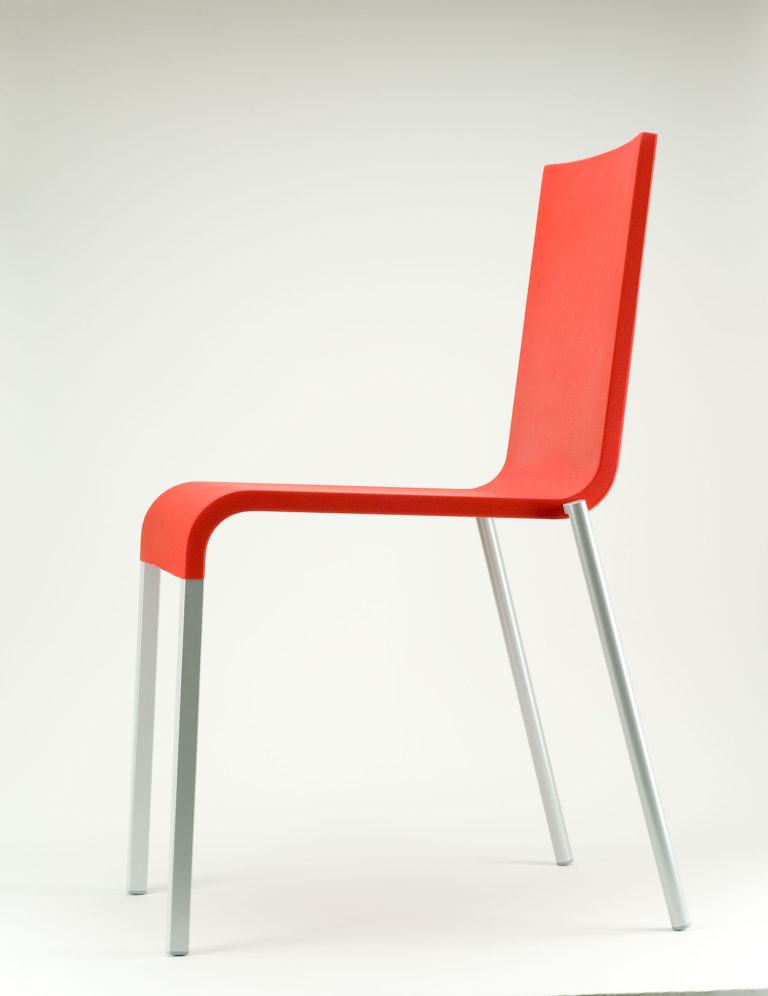 Chair with a molded red plastic seat and back and four aluminum legs.