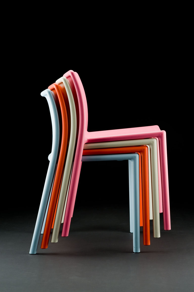 Four simple plastic chairs stacked together, each a different color: white, pink, pale blue, and orange.