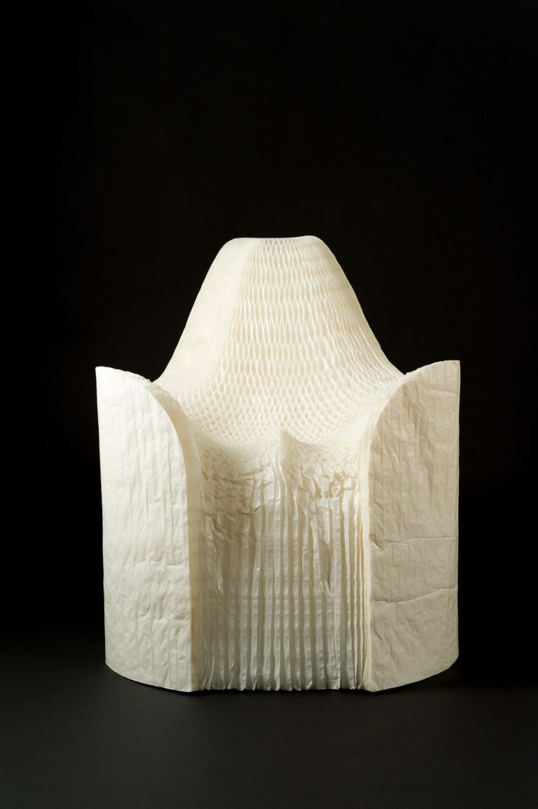 Armchair of thousands of sheets of pleated white paper.