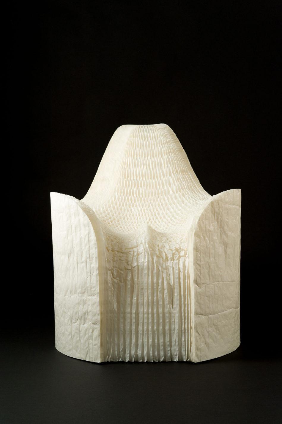 Fauteuil composé de milliers de feuilles de papier blanc plissées.